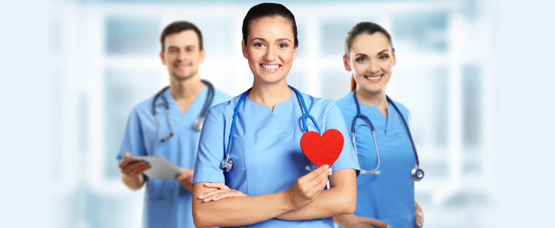 Young female doctor with red heart and medical team on blurred background